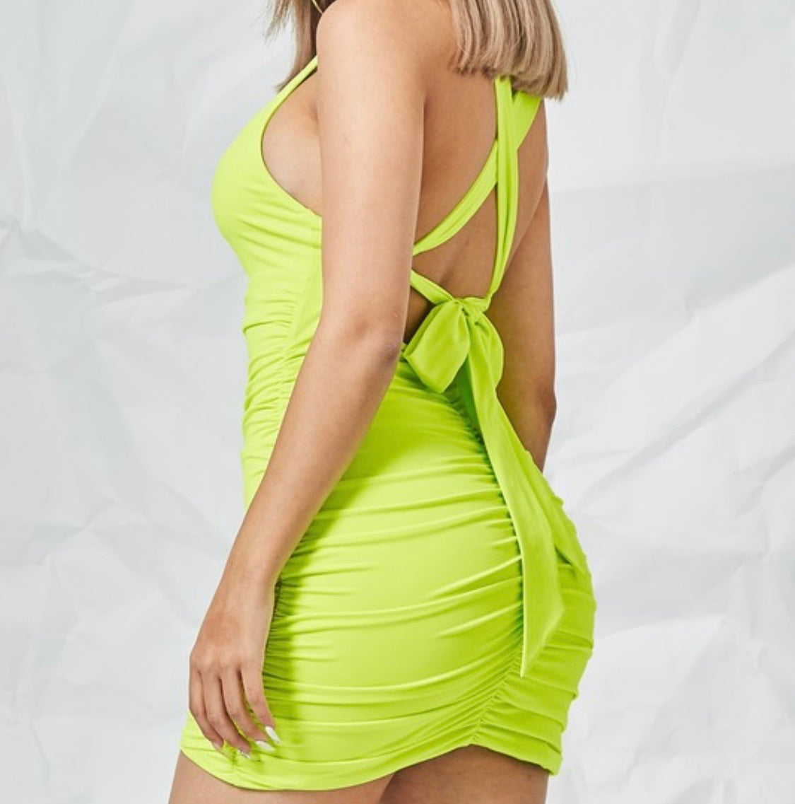 IN THIS IMAGE YOU CAN SEE A YOUNG WOMAN WEARING A  Front Cut-Out Mini Dress. THE BOTTOM SKIRT AREA IS RUCHED. THE DRESS HAS A BACK TIE CLOSURE.  IT IS MADE UP OF 90% polyester AND 10% Spandex.