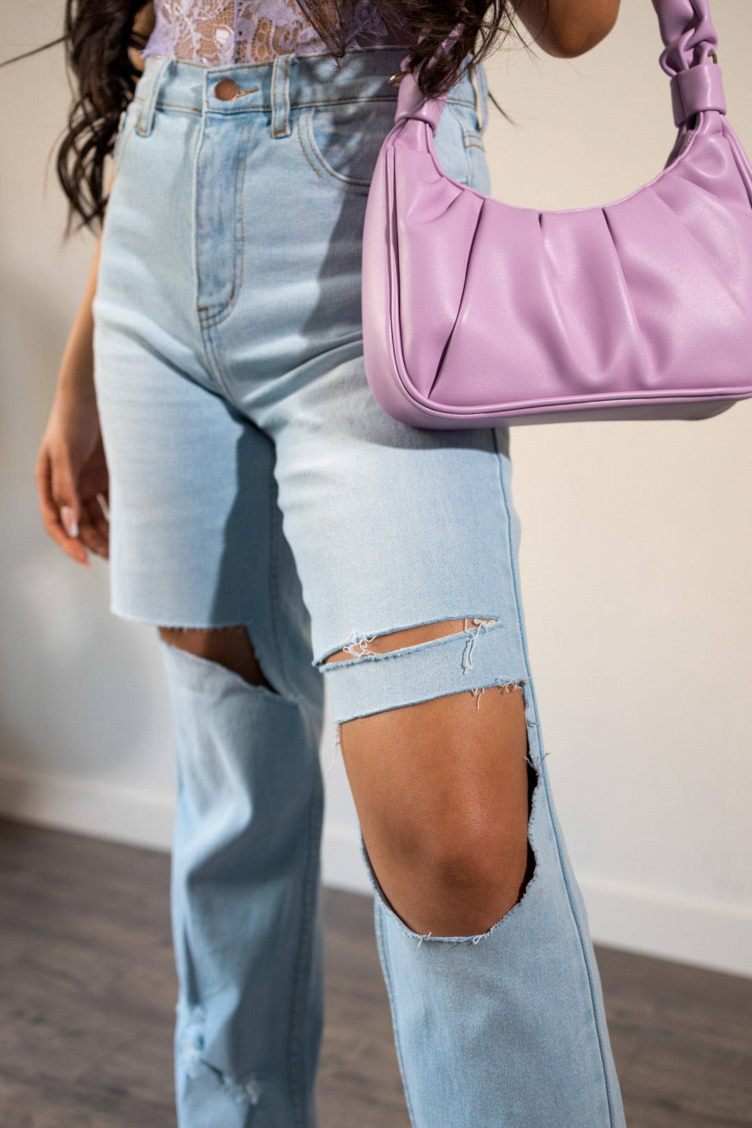 IN THIS IMAGE YOU WILL SEE A WOMAN STANDING UP MODELING A High rise wide leg jeans with distressed details on both front legs of jeans. IT IS  Stone washed . JEANS HAS  Light stretch. IT IS MADE UP OF  99% Cotton &  1% Spandex.   Model IS wearing A  size 5 .  Model'S height IS 5'6