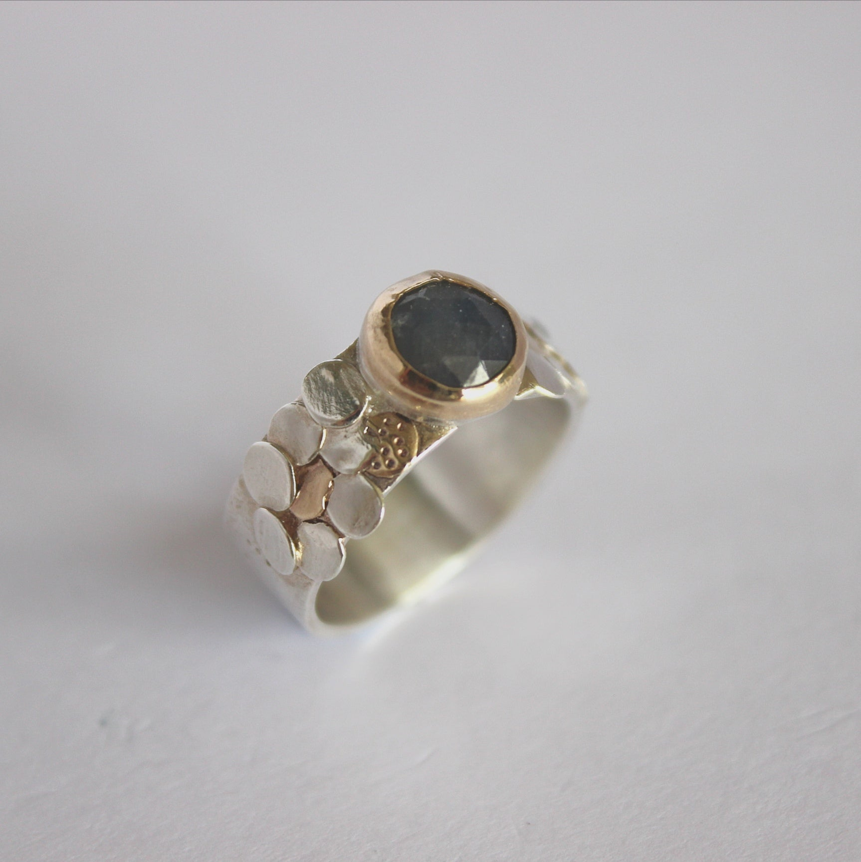 Deep blue sapphire ring with silver and gold scales