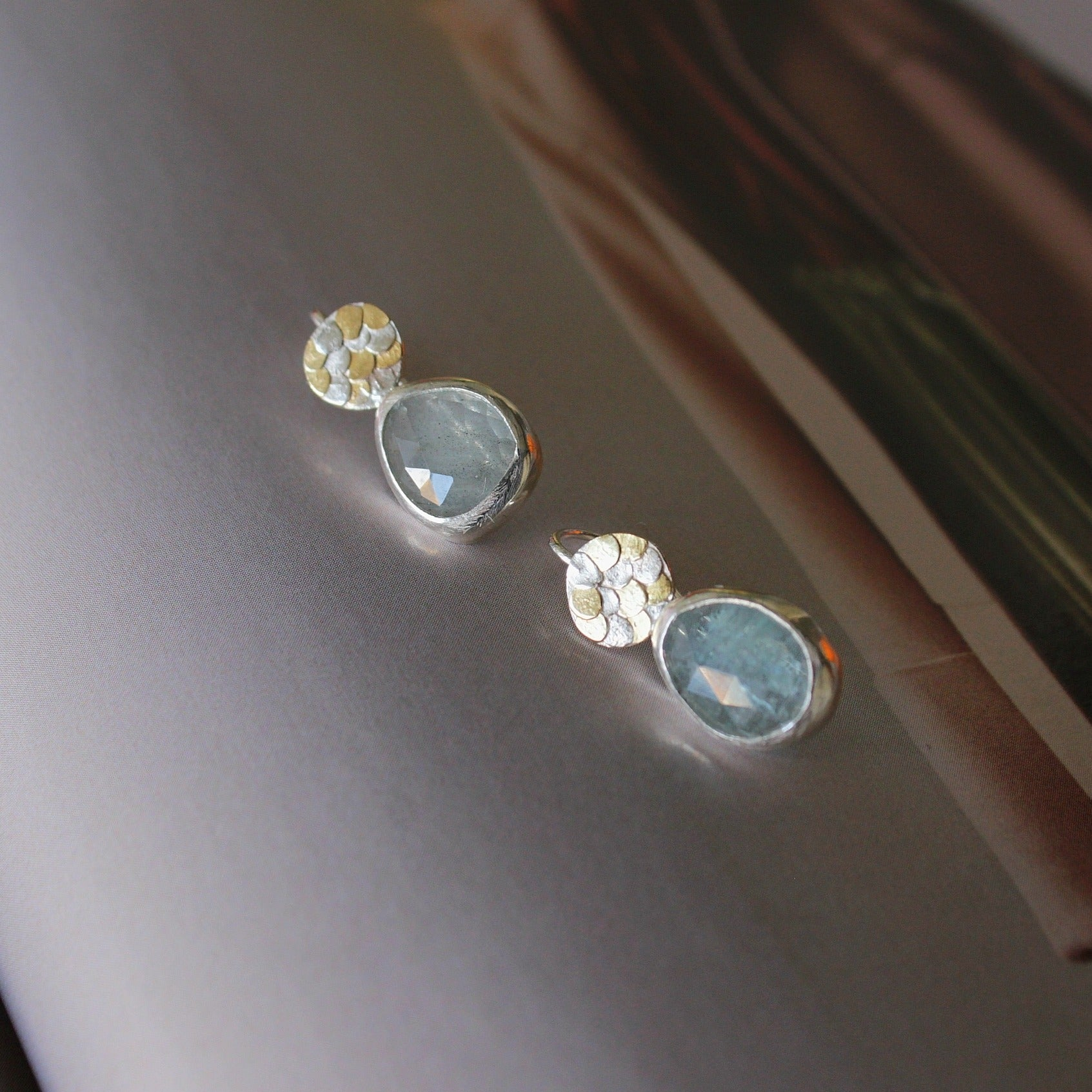 The handcrafted Aquamarine Siren drop earrings by Josie Mitchell Jewellery are one-of-a-kind and completely unique. The vibrant Aquamarines are full of magic and remind us of crystal clear Mediterranean waters. The earrings include Josie's signature Siren scale detailing at the top for the most magical pair of earrings..