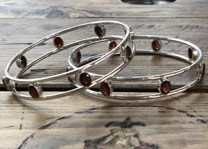 Solid silver hand-made bracelet set with facet cut dark red garnets