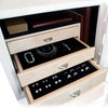 A compact jewelry safe painted a glossy antique white and furnished with a stainless electronic lock and curly maple wood. Luxury upgrades include half moon drawer pulls, necklace rack, and  sand ultrasuede fabric interior.