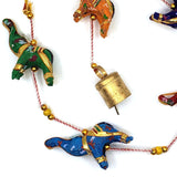 Brass colored bell on the end of an elephant garland.