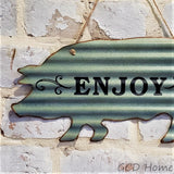 "Gray ""Enjoy"" Tin Sign Shaped as a Pig Hanging on a White Brick Wall."