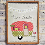 "Retro Camper ""Live Simply"" Wooden Wall Decor hanging on a gray brick wall."