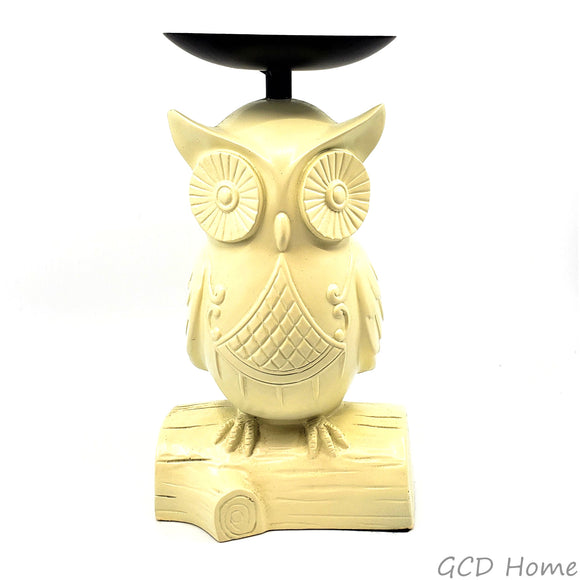 Cream colored owl shaped pillar candle holder with a black metal candle plate.