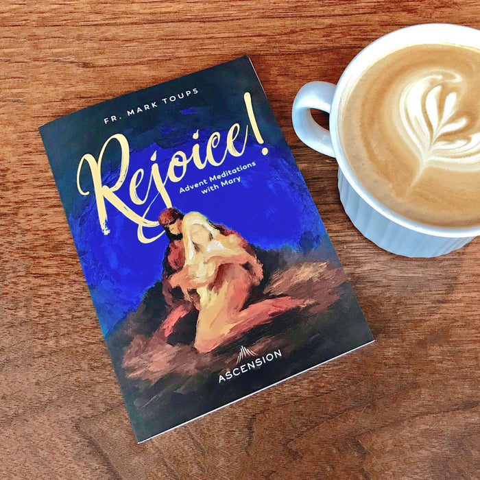 A copy of the Catholic journal, Rejoice! Advent Meditations with Mary by Fr. Mark Toups and Ascension on a wooden table next to a cappuccino.