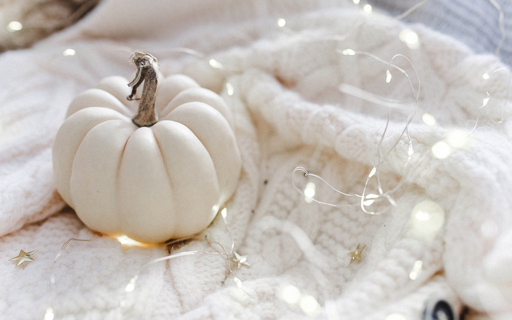 White pumpkin surrounded by string lights