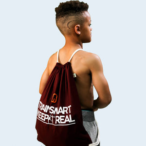Model shot of a child wearing the burgundy Train Smart Keep It Real drawstring bag. TSKIR