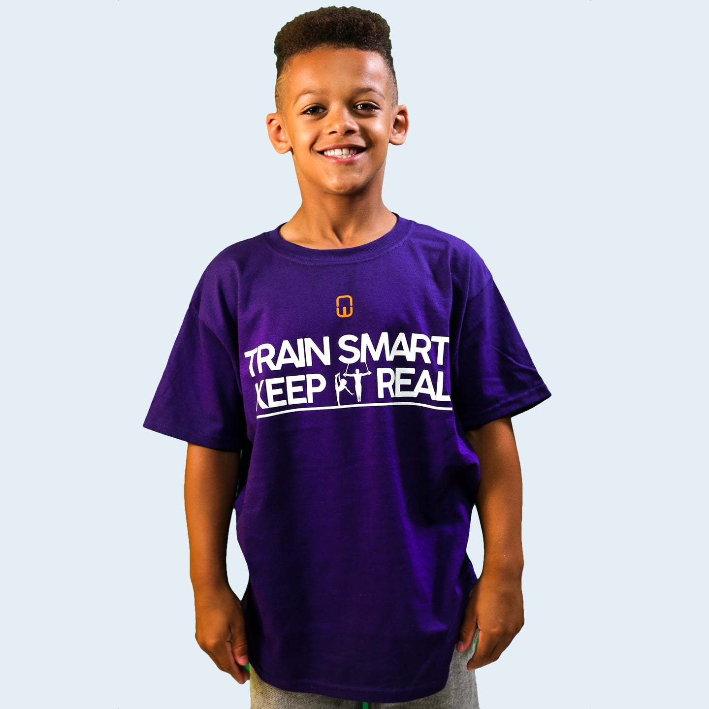 Model shot of a male child wearing a purple Train Smart Keep It Real logo T-Shirt. TSKIR