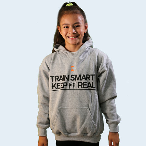 Model shot of a girl wearing a grey children's hoodie. With the Train Smart Keep It Real logo on the front. TSKIR