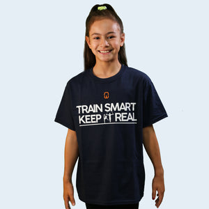 Model shot of a female child wearing a navy blue Train Smart Keep It Real logo T-Shirt. TSKIR