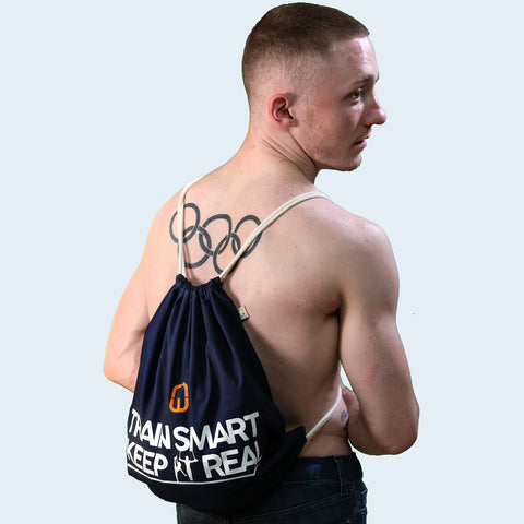 Model shot of a Nile Wilson wearing the Navy Train Smart Keep It Real drawstring bag. TSKIR