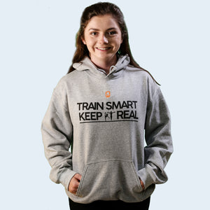 Model shot of Joanna Wilson wearing an adult grey Train Smart Keep It Real logo Hoodie. TSKIR