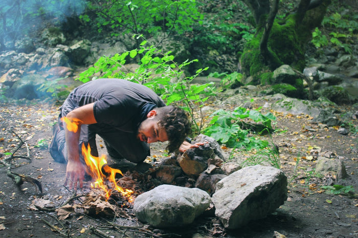 man building a fire for survival