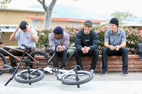 Premium team riders sitting on a ledge with their bikes