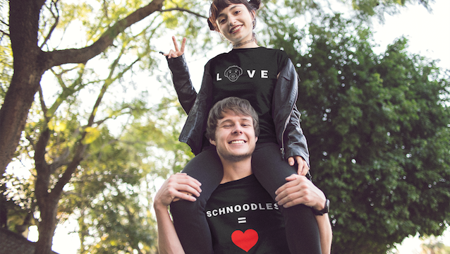 """Woman sitting on man's shoulders posing for a photo, both wearing T-Shirts from the """"Love"""" collection at The Schnoodle Show."""