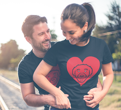 """One man and one woman posing for a romantic photo wearing """"Schnoodle Heart"""" T-Shirts from The Schnoodle Show."""