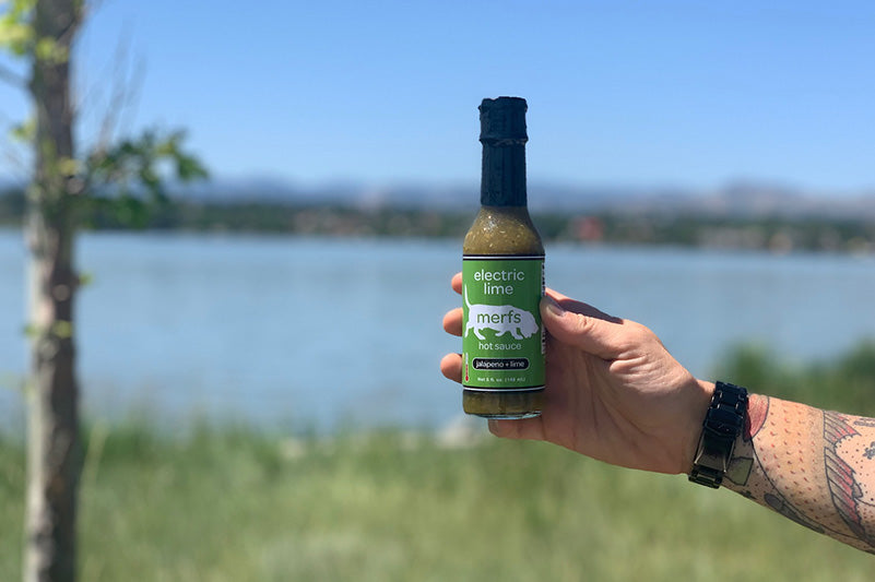 Holding a bottle of electric lime hot sauce outside