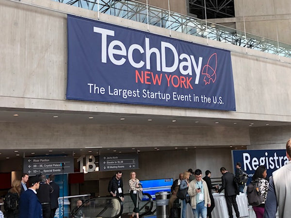 "large blue banner that reads, ""Tech Day New York. The largest startup event in the U.S."""