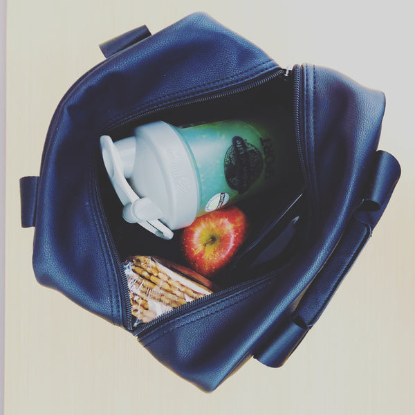 top view of an open T|W lunch tote with crackers, an apple and resusable water bottle