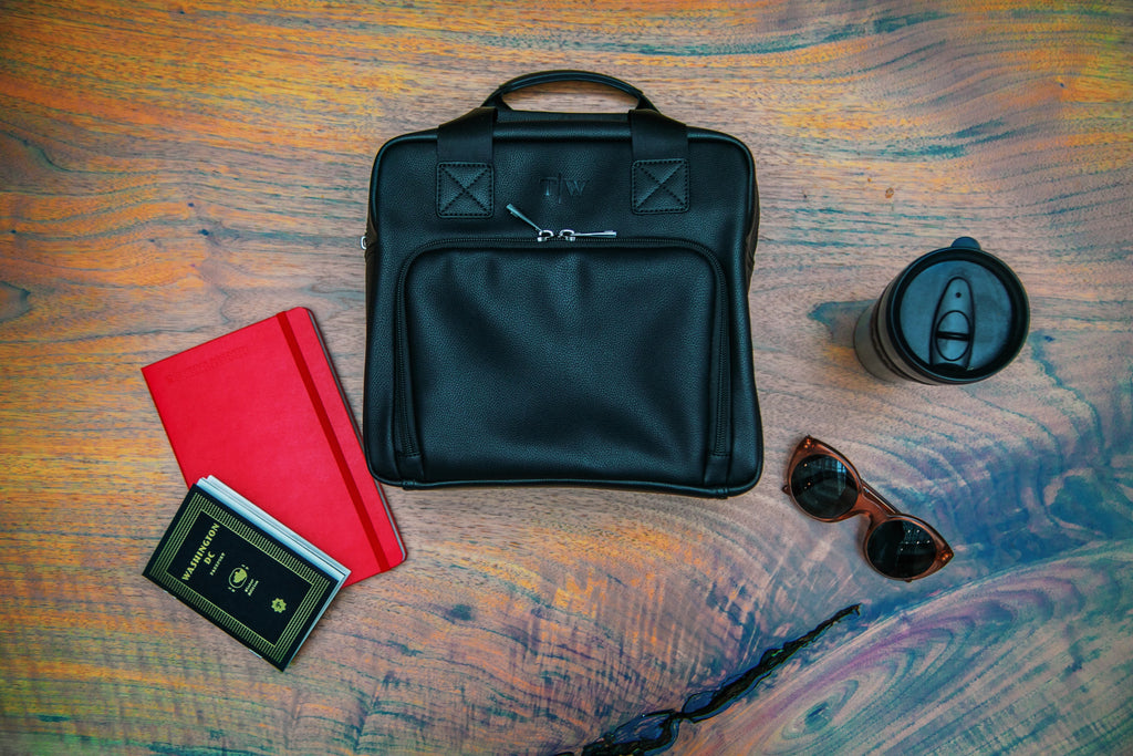 T|W lunch tote in the middle of a red notebook, black coffee mug and sunglasses