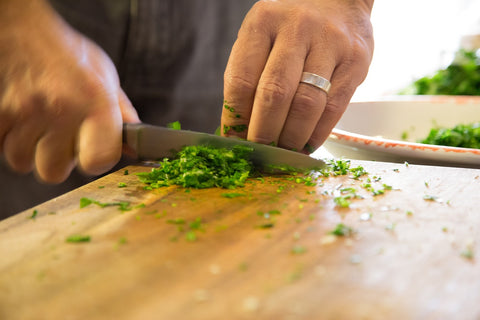 Man chopping a leafy green vegetable on a cutting board