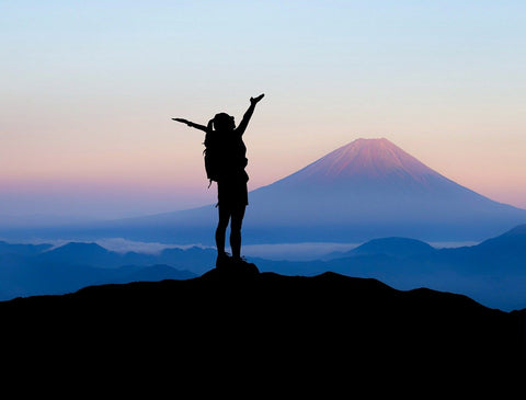Human silhouette standing atop a mountain, arms raised