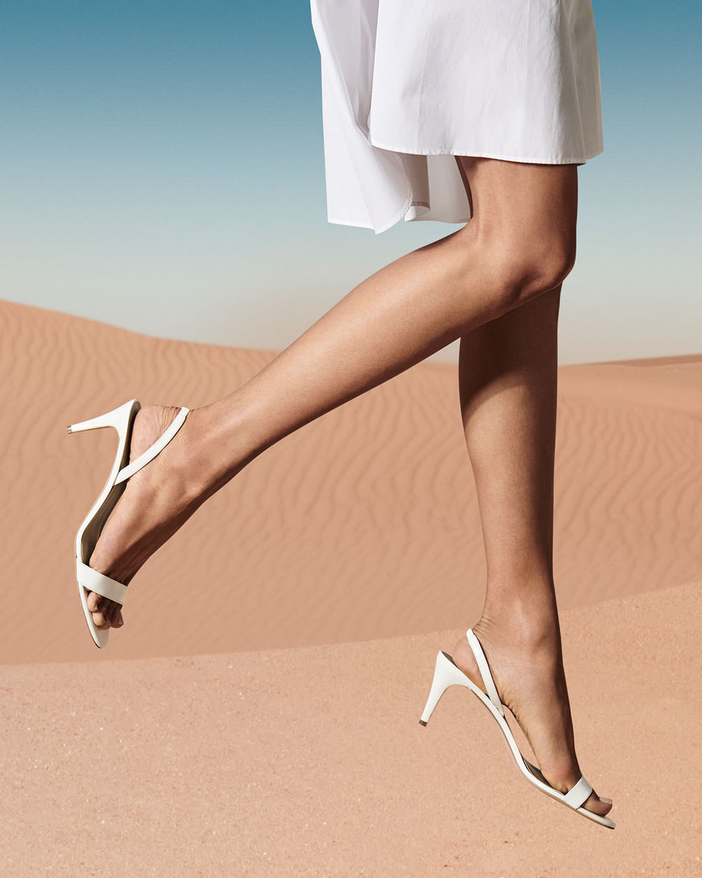 AERA Campaign. Legs with white AERA shoes jumping in the desert
