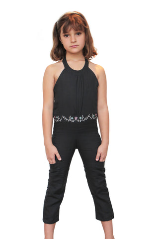 Sweet 8 year old wearing a 6 year old sized Dark Grey linen one piece long leg length jumpsuit with a halter top and tie fastener behind the neck, and a waist band of embroidered pink and white flowers all around front and back of the waistband. and a flap front pocket on both mid legs.
