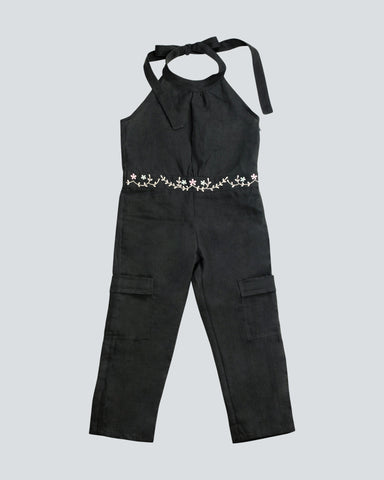 Dark Grey linen one piece long leg length jumpsuit with a halter top and tie fastener behind the neck, and a waist band of embroidered pink and white flowers all around front and back of the waistband.