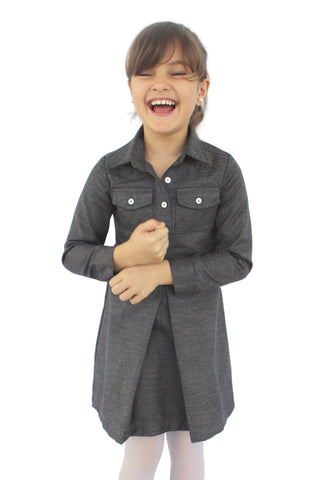 Photo of a young girl wearing our dark grey blue long sleeved shirt dress. It has a pocket on each breast area and a pleat front center of skirt.  It is a short length dress