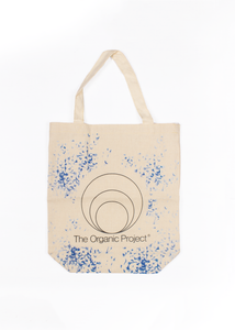 Photo of our natural colored small canvas tote bag with our The Organic Project Logo on front with blue baby flowers all around . perfect for shopping.