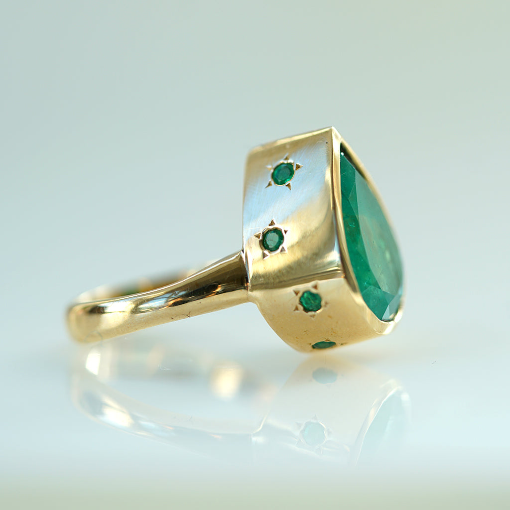 Emerald Pear Shaped Solitaire ring in gold with star Pavé