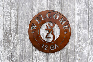 metal sign shaped like end of 12 gauge shotgun shell with a buck in the center and the word welcome