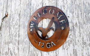 metal sign shaped like end of 12 gauge shotgun shell with a duck in the center and the word welcome