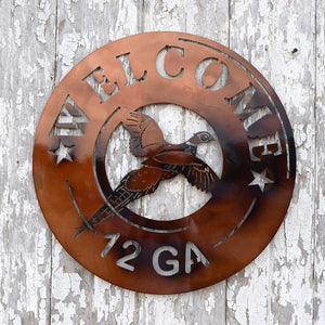 metal sign shaped like end of 12 gauge shotgun shell with flying pheasant in the center and the word welcome