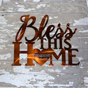 "laser cut metal art with words ""bless this home"" with the ""o"" being a heart containing the family name and established year"