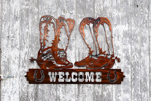 metal sign showing two sets of cowboy boots with spurs resting on a welcome sign with horseshoes