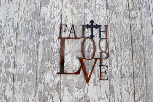 "laser cut metal art of three words, faith, hope, love and letters of each word are chared with the ""t"" being a cross"