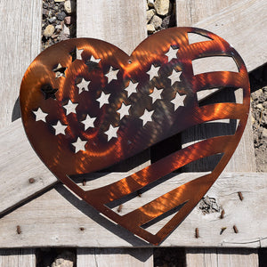 laser cut metal art shaped as a heart with stars in the corner and stripes across the rest to mimic the U.S. Flag