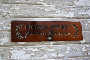"laser cut metal art rectangle with the words, ""Farm Sweet Farmhouse"" and decorative leaves"