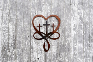 laser cut meatl art depicting three crosses resting in the middle of a heart and an infinity symbol at the base of the heart