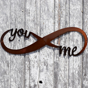 "laser cut metal art with the words, ""you & me"" cut from the infinity symbol"