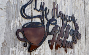 "laser cut metal art showing one steaming hot cup of coffee, three coffee beans and the words ""Life Happens, Coffee Helps""."