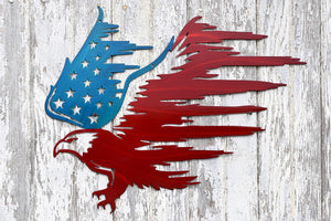 laser cut metal art in the shape of a bald eagle with the back wing painted blue & covered with stars, while the front wing has tattered stripes and is painted red.