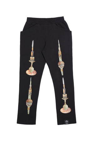 ED. 50 SWEATPANTS WITH BALANCED STACK OF POTTERY AND KNIFE