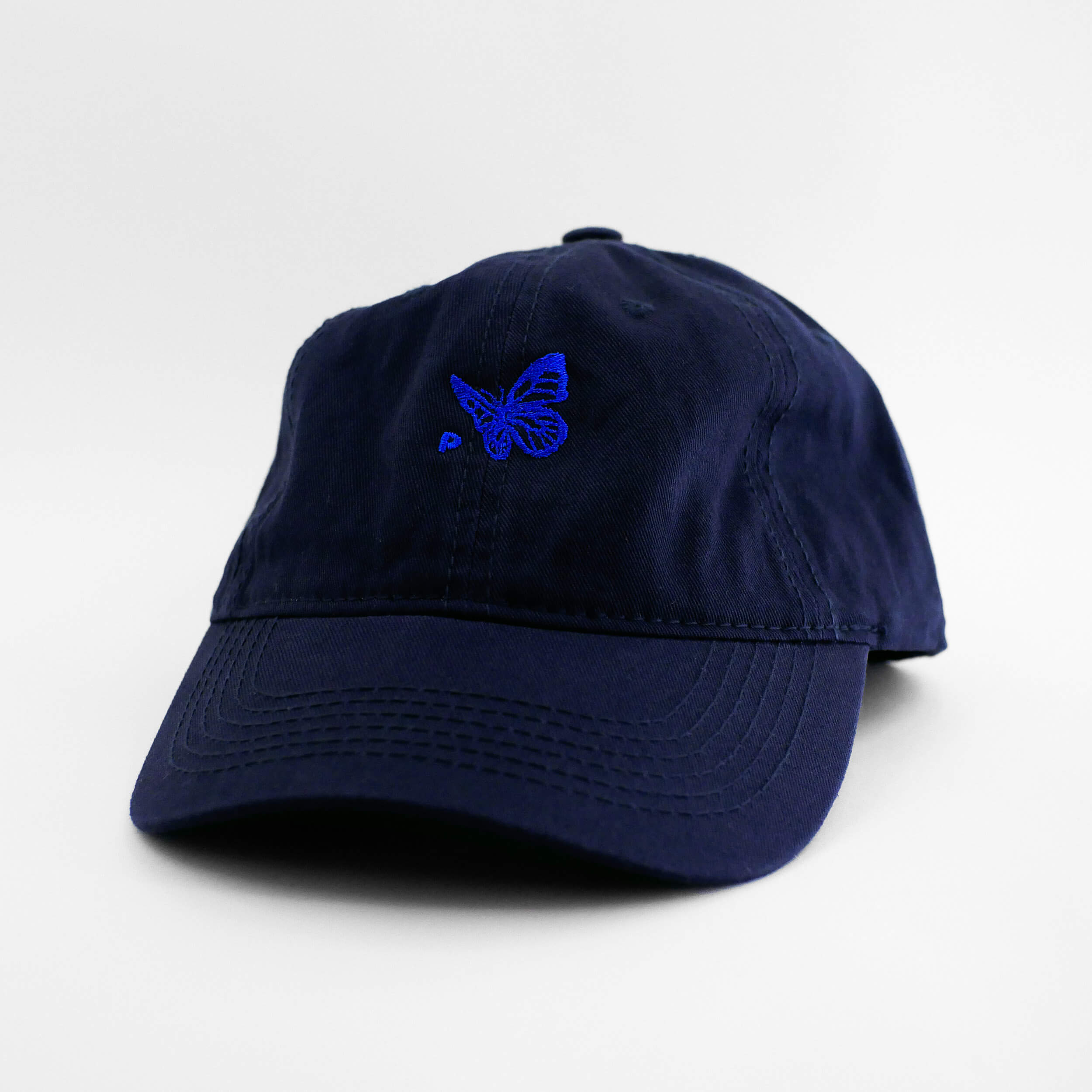 Angle view of the embroidered Buttterfly Logo navy blue dad hat from PHOSIS Clothing