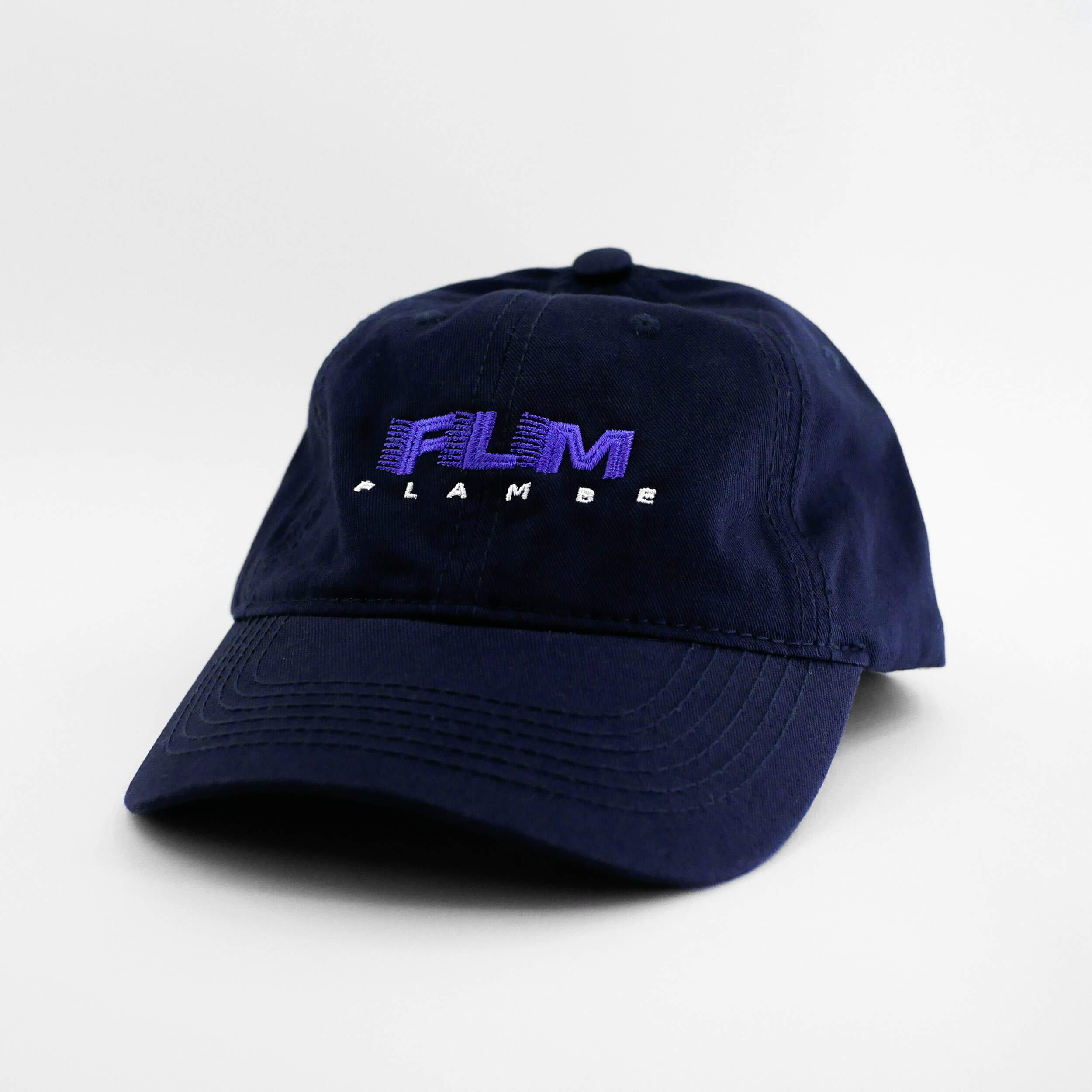 Angle view of the embroidered 'FLAMBE' navy blue dad hat from PHOSIS Clothing