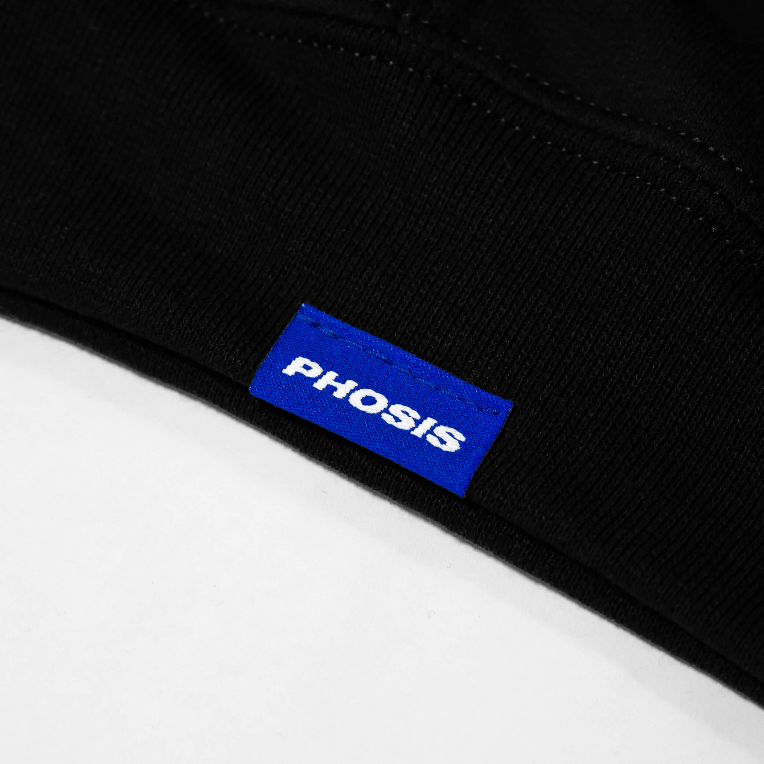 Close up view of the blue woven label in the HOLOCENE black hoodie from PHOSIS Clothing